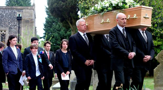 Ronnie Corbett's coffin is carried into the church followed by family members