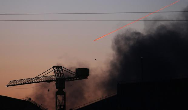 Smoke rises over the shipyard area of east Belfast as a plane flies past in the distance
