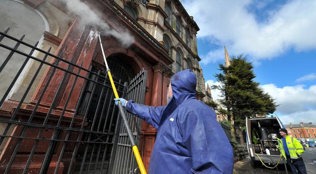 Council workers powerwash the walls of Clifton Street Orange Hall after it was attacked with paint bombs on Sunday