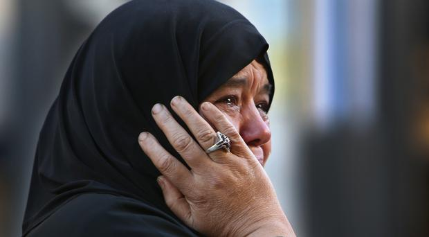 A Syrian refugee, who lives in Lebanon, cries while waiting for some of her relatives to board a bus to Beirut International Airport (AP)