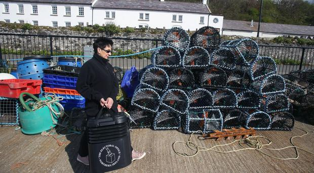 Rathlin Island polling station manager Teresa McCurdy with the ballot box in which the island's population of just over 100 people will cast their votes