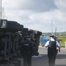 Police officers at the scene of an overturned lorry at the Eglinton Airport roundabout