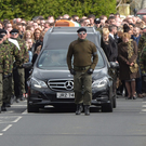 A guard of honour flanks the coffin of Michael Barr at his funeral in Strabane