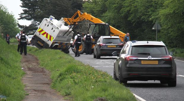 The overturned police Land Rover is lifted upright with a telescopic handle
