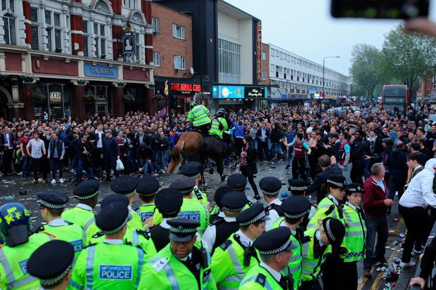 Police confront West Ham supporters who surrounded and threw missiles at the Man United team bus