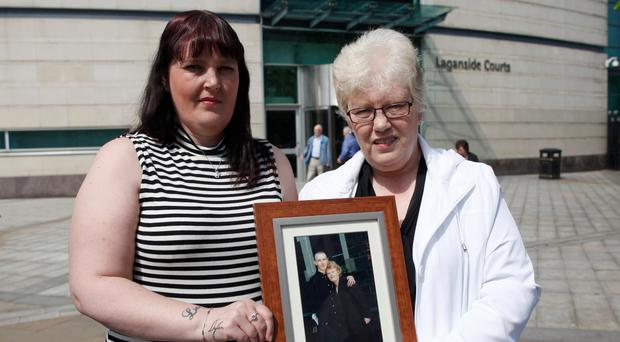 Jonathan's mother Maureen Smith and sister Julie Magee holding his photograph outside court