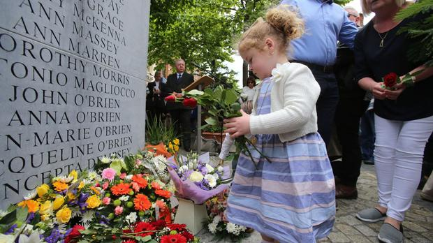 Haley O'Brien (four), whose great uncle John O'Brien was killed in the Dublin-Monaghan bombings, lays a wreath in Talbot Street, Dublin