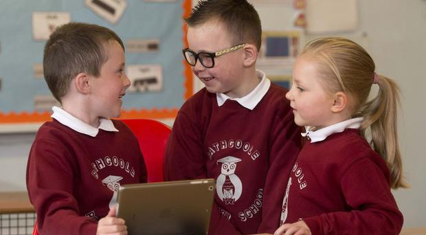 Connor Hamilton, six, uses a school iPad with Clarke McMullan, six, and Sarah Copeland, five, at Rathcoole Primary School, Newtownabbey (Association of Teachers and Lecturers/PA)