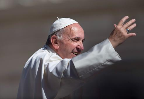 Pope Francis waves to the crowd as he arrives for his general audience in St Peter's Square