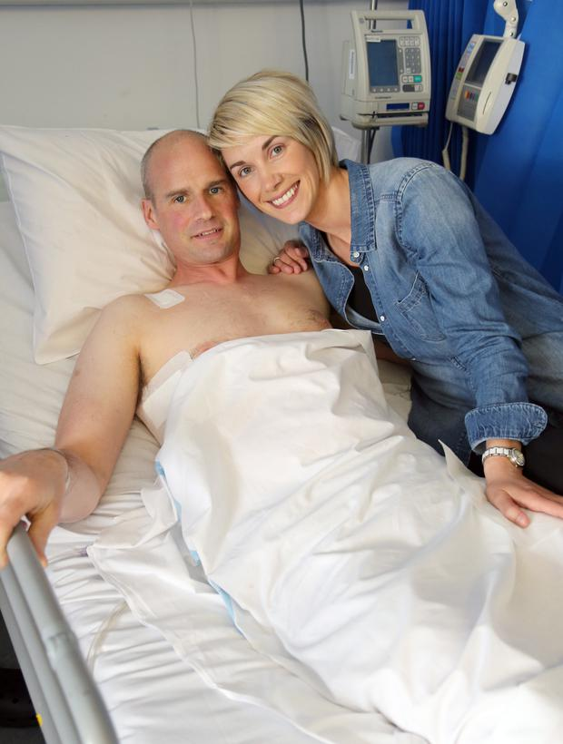 Ryan Farquhar smiling from his hospital bed alongside wife Karen after initially recovering from his injuries