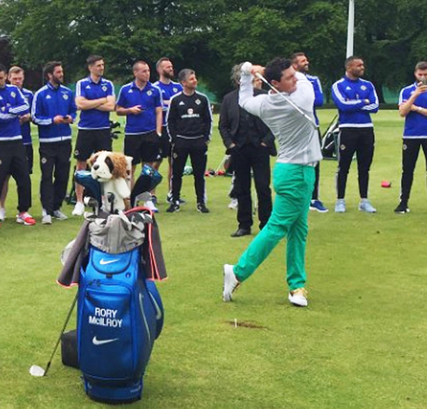 Rory McIlroy playing a shot in front of the Northern Ireland football team