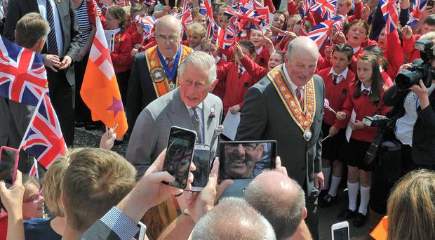 The Prince of Wales meets members of the Orange Order, schoolchildren and local residents during his visit to Loughgall yesterday