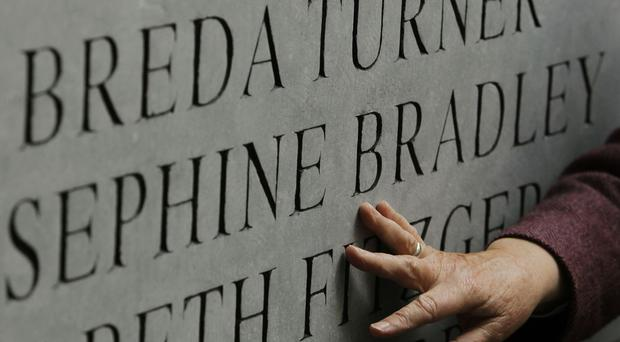 A hand placed on the memorial at a ceremony marking the 40th anniversary of the Dublin and Monaghan bombings