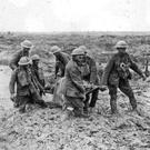 A stretcher party knee-deep in mud as they carry a casualty from a World War One battlefield