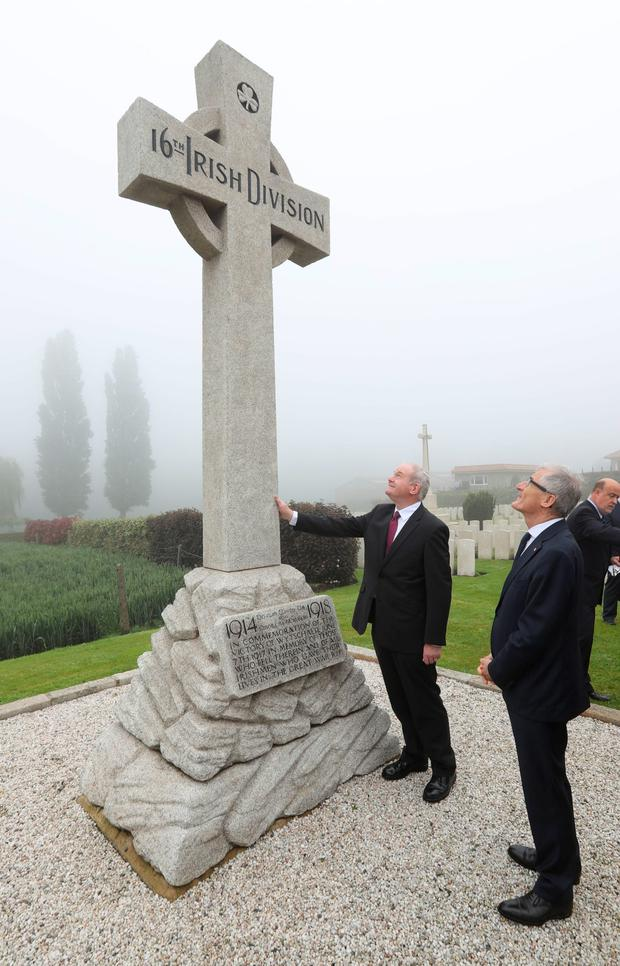 Mr McGuinness touches a memorial to the 16th Irish Division