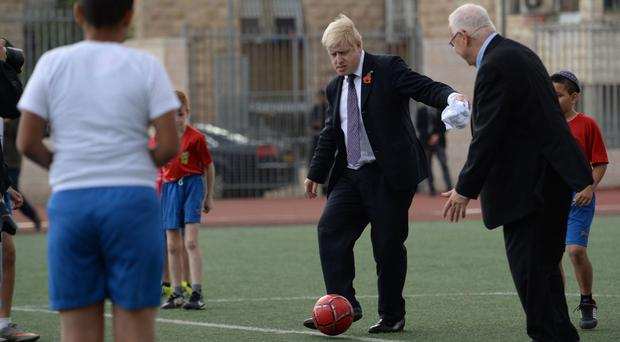 Mayor of London Boris Johnson and Israeli President Reuven Rivlin play football with children at the Equaliser football project in Jerusalem