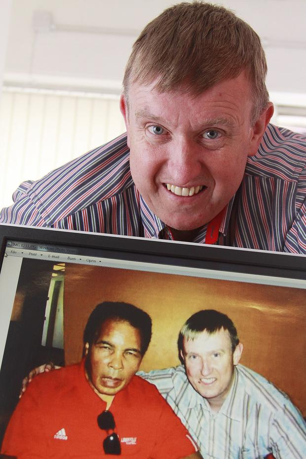 Mervyn Storey with a picture of him and Muhammad Ali