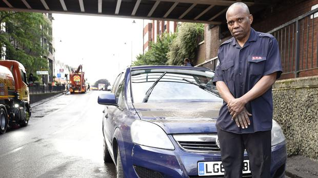 Darlington Imoh, 60, in front of his damaged Vauxhall Zafira which became immersed in water during a flash flood in Manor Road in Wallington, Surrey following torrential rain.