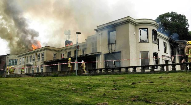 Firefighters attend to the scene of the blaze at Lissue House in Lisburn yesterday