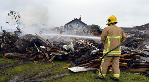 A firefighter douses the smouldering remains of the Edgarstown bonfire in Portadown