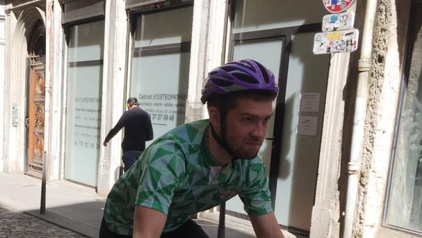 Stephen Collins, a Northern Ireland fan who is cycling the length of France as he follows the team's progress in Euro 2016, on his bicycle in Lyon