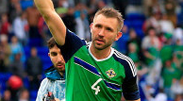 Gareth McAuley salutes the travelling Green and White Army after scoring in Northern Ireland's historic win over Ukraine on Thursday night