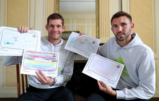 Northern Ireland players Michael McGovern and Gareth McAuley read the messages of support