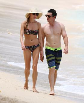 Rory McIlroy and fiancee Erica Stoll stroll along a beach