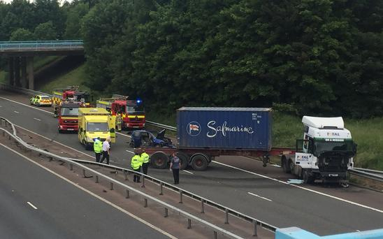 Emergency services at the scene of a crash involving a car and a lorry on the M2 yesterday near the Dunsilly roundabout