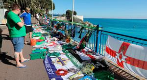 People stand next to tributes for Northern Ireland fan Darren Rodgers who died in Nice during Euro 2016