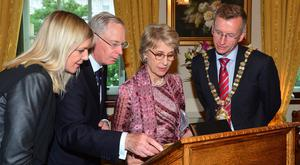 Belfast Lord Mayor Brian Kingston and Suzanne Wylie, chief executive of Belfast council, watch as the Duke and Duchess of Gloucester sign the visitors' book at the City Hall yesterday. The royal couple were guests at a civic dinner to mark the centenary of the Battle of the Somme
