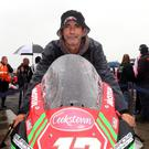 Malachi Mitchell-Thomas' father Kevin sits on one of his son's race bikes before the tribute