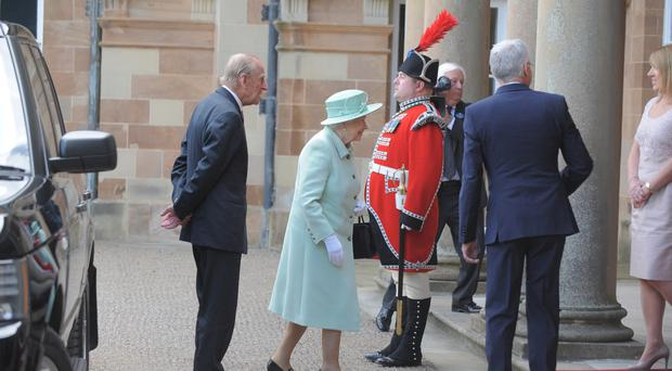 Queen Elizabeth II and Prince Philip arrive at Hillsborough Castle yesterday where the royal couple met invited guests
