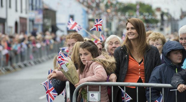 Crowds wait for the arrival of the Queen and Duke of Edinburgh in Bushmills Village