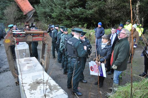 Police line up while concrete blocks are placed at the site during the protest over the drilling