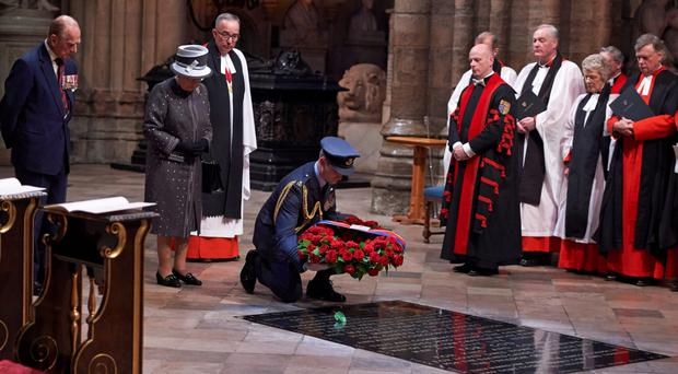 A member of the military lays a wreath made of roses and bay leaves on the Grave of the Unknown Warrior on behalf of Queen Elizabeth II (2nd from left) and Prince Philip, Duke of Edinburgh (left) at a service on the Eve of the centenary of the Battle of the Somme at Westminster Abbey