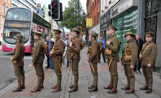 Young men dressed in WW1 soldiers' uniforms marching in file in Belfast yesterday in honour of victims of the Somme