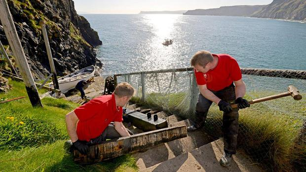 Work being done to replace a crane to lift a fishing boat from the water on to the rocky Carrick-a-Rede island (National Trust/PA)