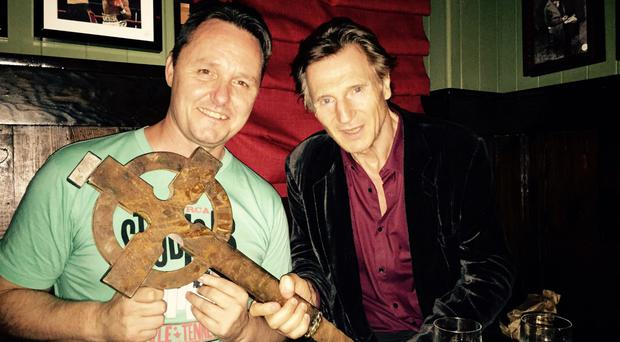 Sean Muldoon, one of the Irish owners of the Dead Rabbit bar in New York with Liam Neeson and the Celtic cross he carried in the movie Gangs of New York
