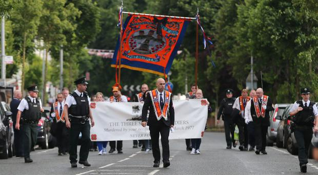 Orange Order members march on Woodvale Road in Belfast