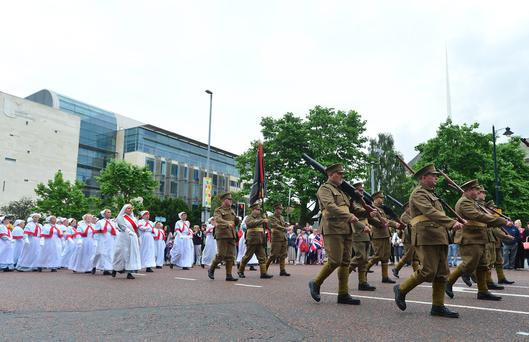 Members of the public watch Orangemen and bandsmen in Belfast City Centre as they take part in the annual Twelfth of July parade in Belfast. Pacemaker