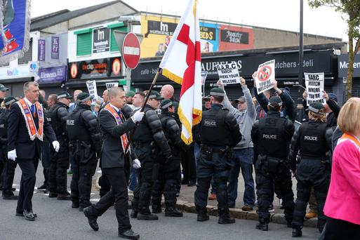 Police stand between Orange Order members and nationalist protesters at the Ardoyne shops on Tuesday