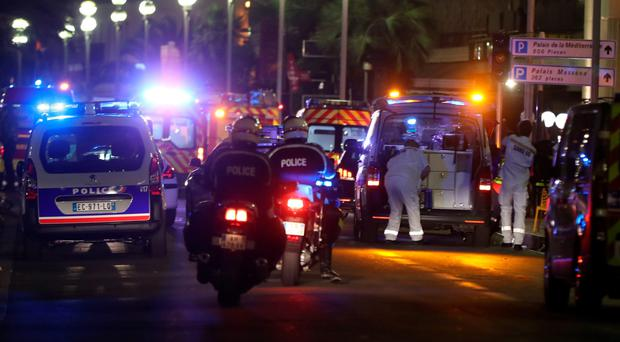 Police officers and rescue workers at the scene after a lorry ploughed into a crowd leaving a fireworks display in Nice