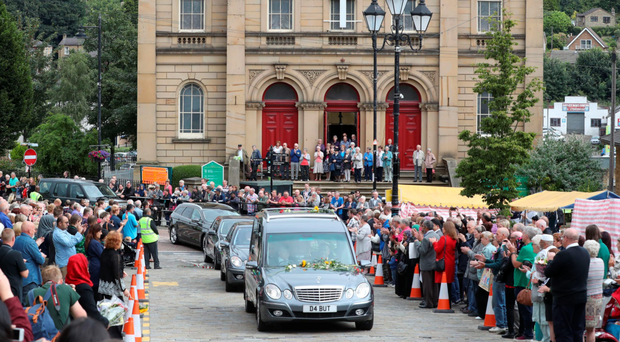 Pupils and staff of Norristhorpe Junior and Infant at School in Heckmondwike hold white roses as they watch the cortege for Labour MP Jo Cox pass in her Batley constituency in West Yorkshire, ahead of her private funeral service