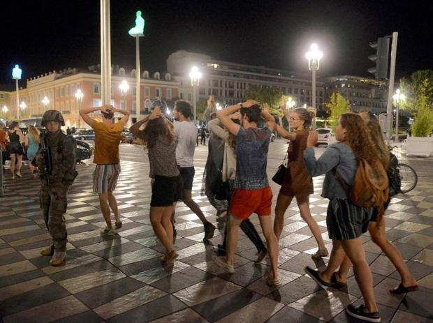 Young people walk with their hands up after the French army moved in to secure Nice following the attack