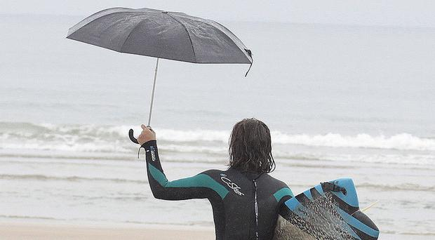 A surfer in Portstewart shelters from the rain