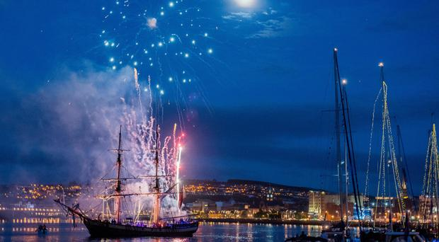 Fireworks explode behind the tall ship The Phoenix