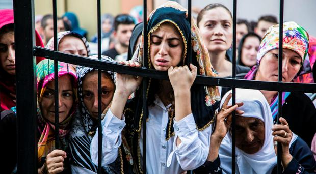 Women react during the funeral of a victim