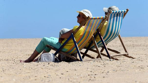 A couple relax in deckchairs on the beach at Great Yarmouth, Norfolk, as a mini heatwave brings the hottest temperatures of the year