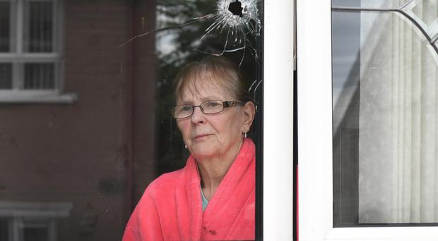 Vera Smyth looks at the damage caused to her home in the Turf Lodge area of west Belfast after a gun attack early yesterday